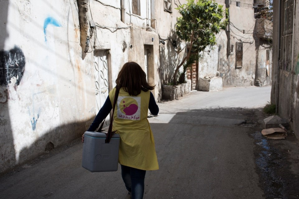 ©UNICEF/2016/Damascus-Syrian Arab Republic/Nader A community health volunteer carrying polio vaccination kit heads out to immunize children from door -to- door in Damascus City, 16 March 2016.