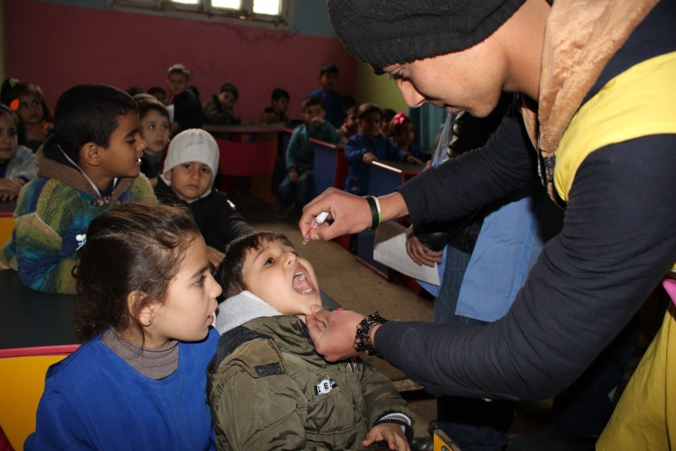 ©UNICEF/2016/Qamishli-Syrian Arab Republic/Masoud A community volunteer, who is a part of mobile health team, administers polio vaccine in a Pre-School, Qamishli City, 16 March 2016