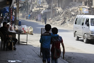 On 24 August 2016 in the Syrian Arab Republic, two children walk arm in arm down a war damaged street in Aleppo. By end August 2016, children continue to bear the brunt of the latest surge in violence in Aleppo.  In the eastern part of Aleppo, around 100,000 children remain trapped since early July.  Water has ceased flowing through the public network, as the generator that operates the main water pumping station needs urgent repairs.  UNICEF does not have safe access to provide the urgent humanitarian assistance needed in the area. In the western part of Aleppo, an estimated 35,000 people were displaced when new waves of fighting hit the al-Hamadaniyah neighbourhood.  Already displaced by the war and living in half-built apartment towers, again families had to flee and leave everything behind.  Most families are currently staying in informal shelters such as schools and mosques as well as in parks and on the streets.  UNICEF trucks in water daily for 300,000 of the most vulnerable people including newly displaced families in informal shelters. The main electricity network that powers pumping stations sustained damage in recent fighting. UNICEF supports the delivery of fuel to operate generators for water pumping stations and groundwater wells that provide safe drinking water to around 1.2 million people.