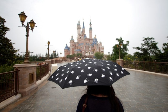 A woman holds a Mickey Mouse umbrella as she visits Shanghai Disney Resort during a three-day Grand Opening events in Shanghai, China, June 15, 2016. REUTERS/Aly Song