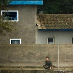 A North Korean soldier sits in front of a building at the bank of the Yalu River, near the North Korean town of Sinuiju, opposite Dandong in China's Liaoning province, September 10, 2016.  REUTERS/Thomas Peter