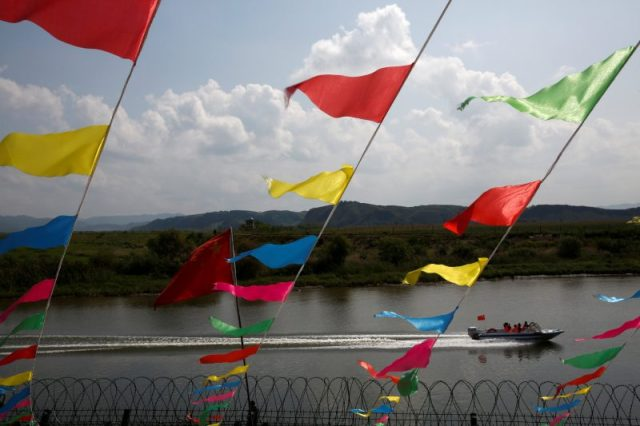 A boat carries tourists along the Yalu river between North Korea (background) and China, outside the Dandong, Liaoning province, September 11, 2016. REUTERS/Thomas Peter