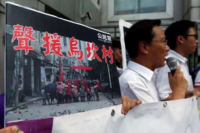 "Protesters demonstrate with a placard which reads ""Support Wukan village"" outside China Liaison Office in Hong Kong, China September 14, 2016.      REUTERS/Bobby Yip"