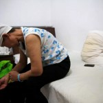 Huang sits on a bed in her room at the accommodation where patients and their family members stay while seeking medical treatment in Beijing, China, June 22, 2016. REUTERS/Kim Kyung-Hoon