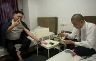 Xiao Jiguo (right) and Zhang Daiming smoke cigarettes in a hotel in Dongguan, Guangdong province, Nov. 9, 2016. Kevin Schoenmakers/Sixth Tone