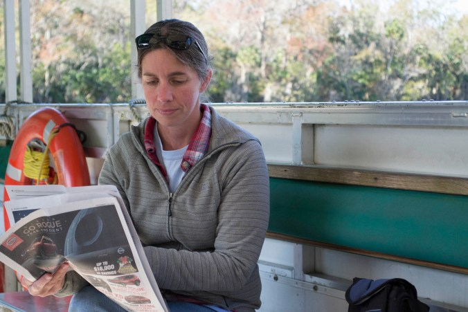 This De Leon Springs Park Ranger takes a break to catch up on the news while she waits on her next group of boat passengers. Photo taken December 11, 2016, at De Leon Springs State Park, by Chrissy Clary.