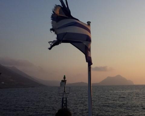 Zerfledderte Griechenlandflagge weht im Wind bei Schiffahrt in Ägais