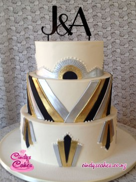 3 tier Art Deco white with gold, silver and black styled wedding cake with the letters J&A as toppers