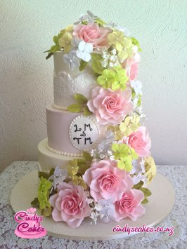 3 tier elegant wedding cake with pink sugar flowers and green sugar leaves flowing from top to bottom. A badge with the text L.M & T.M is pinned on the front.