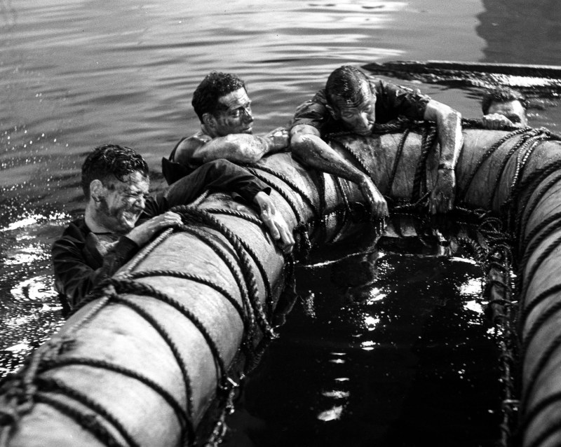IN THE AFTERMATH OF THE EXPLOSION CAPTAIN KINROSS (NOEL COWARD) , 2ND RIGHT, ATTEMPTS TO GET INTO THE LIFEBOAT. *** Local Caption *** Feature Film