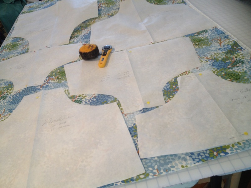 Apron patterns of various sizes from babies to adult laid out to be cut
