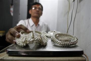 A silver trader weighs his silver ornaments inside his shop in the western Indian city of Ahmedabad