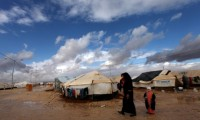 A Syrian refugee walks with her two kids at Za'atari Syrian refugee camp, near the Syrian border in Mafraq, Jordan. Photograph: Mohammad Hannon/AP
