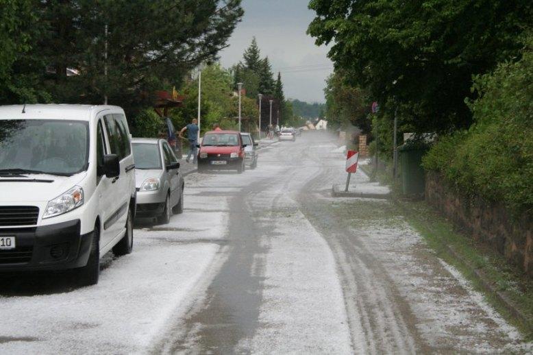 Weiß von Hagelkörnern ist eine Straße in Ansbach (Bayern) am 29.05.2016 nach einem Unwetter. Neben Hagel hatten schwere Regenfälle zu Überschwemmungen geführt. Foto: Mathias Neigenfind/dpa +++(c) dpa - Bildfunk+++