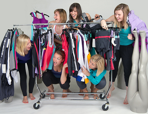 Retail employees trying on merchandise on clothing display rack
