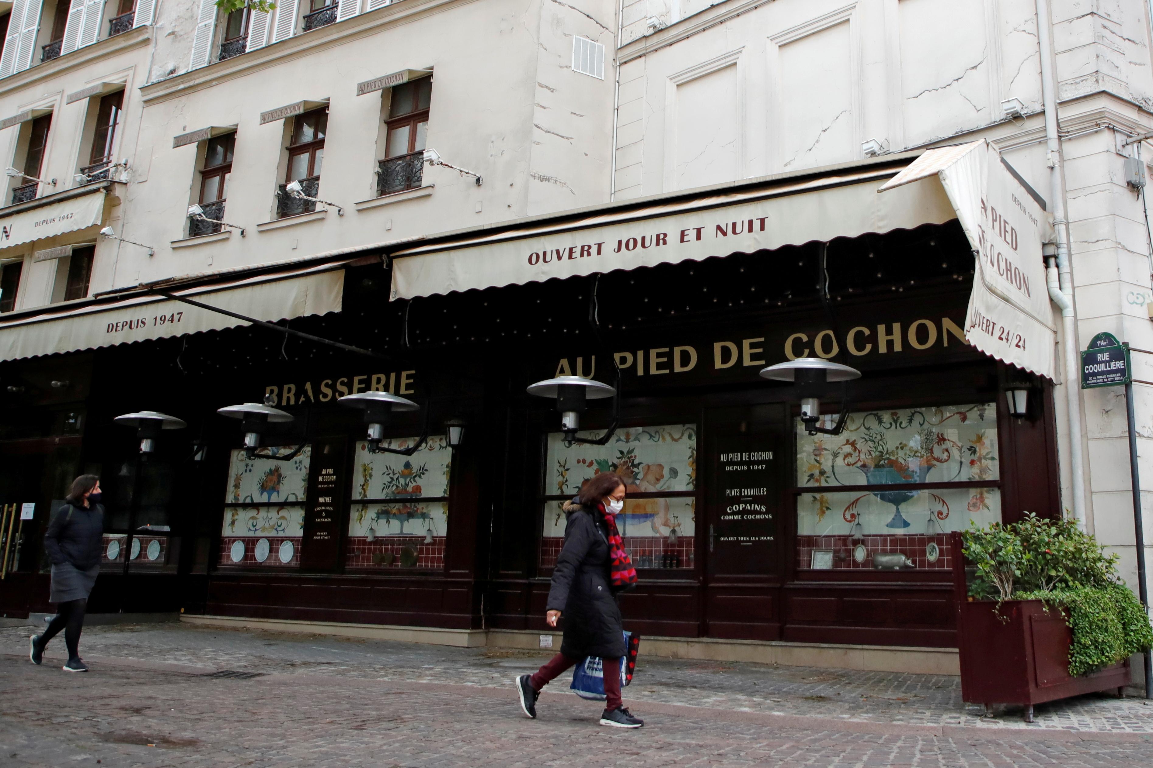 Personas, con máscaras protectoras, pasan frente a un restaurante cerrado en París en medio del brote de la enfermedad por coronavirus (COVID-19) en Francia, el 6 de mayo de 2021. REUTERS / Sarah Meyssonnier