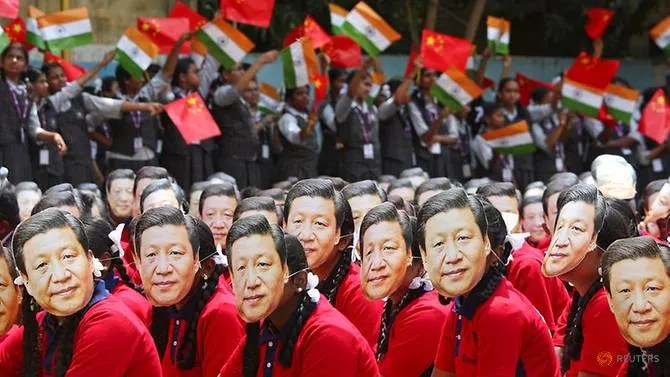 Students wear masks of China's President Xi Jinping as other waves national flags of India and