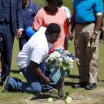 Miles Scott, son of the late Walter Scott, lays a rose as relatives and friends gathered to remember Scott, at Live Oak Memorial Gardens in Charleston, South Carolina, April 4, 2016. REUTERS/Randal Hill
