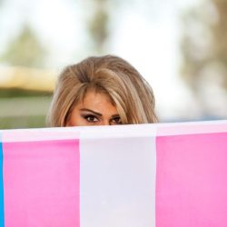 Hispanic Transgender female hiding half her face with Transgender Pride flag.