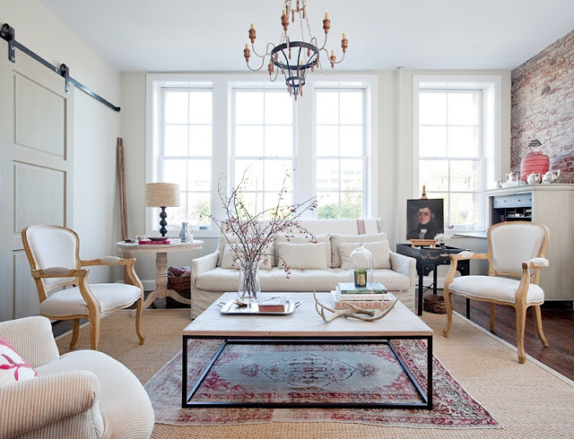 Living room with exposed brick wall, chandelier, large windows, white sofa with matching armchair and two white Louis XIV chairs