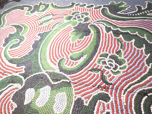 close up of green, red and black beadwork table top by Michael von Selow