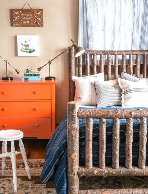 Preppy cabin style bedroom with tree branch bed frame, orange dresser and brass lamp