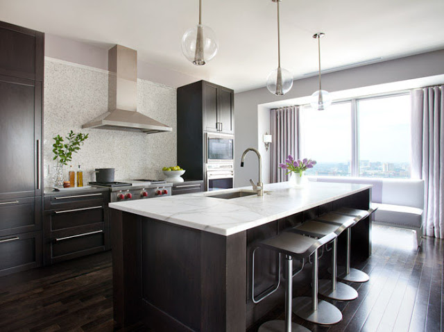 Kitchen with dark wood floor and cabinets with long silver drawer pulls flush to the ceiling, a tile backsplash, three pendant lights, stainless appliances and an island with a marble counter top with silver bar stools with low backs