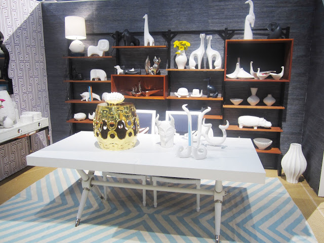 white dining table with lots of small sculptures and candle stick holders on light blue chevron rug at Jonathan Adler's nyigf booth