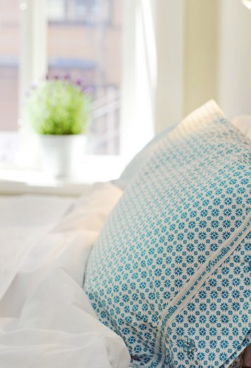 Close up of the white and turquoise patterned pillows