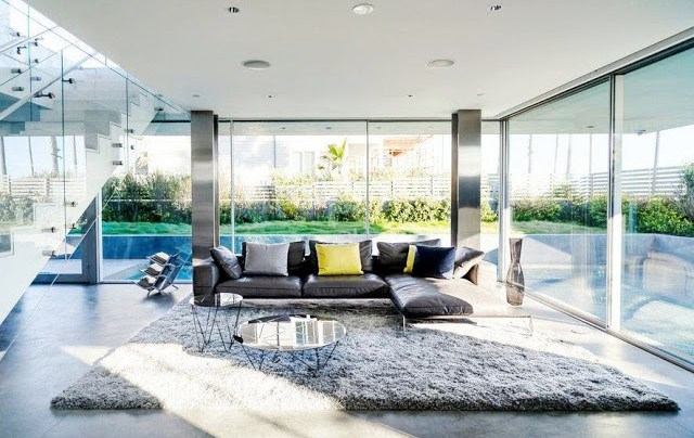 Modern family room with stainless steel columns, grey shag rug, and floor to ceiling windows in the Flip Flop House