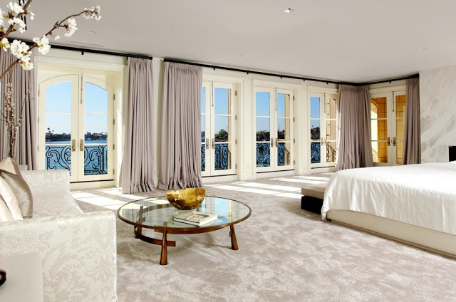 master bedroom with an ocean view,  floor length light purple curtains, french doors, a round glass table, a white sofa and a white bed