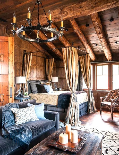 Log cabin bedroom with an iron chandelier, blue velvet sofa and canopy bed