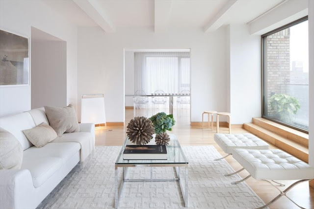 reverse view of living room in New York Ciry penthouse with white sofas, light wood floor, a white rug and a glass coffee table