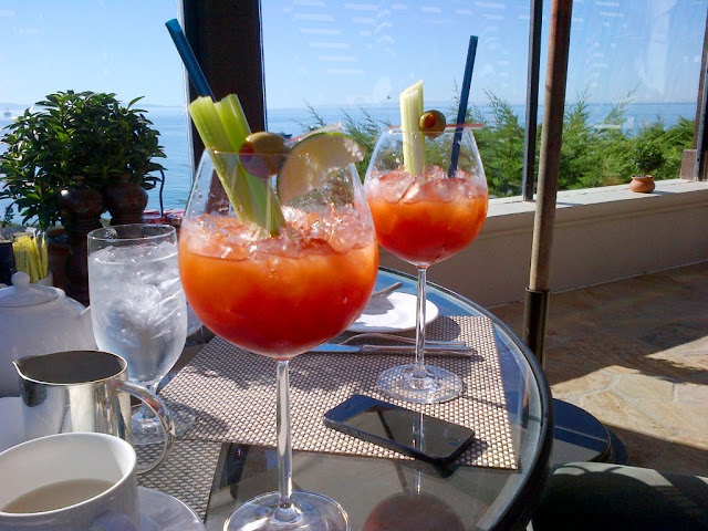 Bloody Mary's sitting on a glass table on a patio with an ocean view