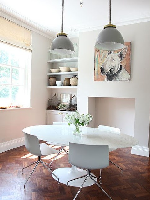 breakfast nook in a country house in the UK with white tables and chairs, a painting of a bull terrier hanging over what was once a fireplace, gray walls, and walnut herringbone wood floors