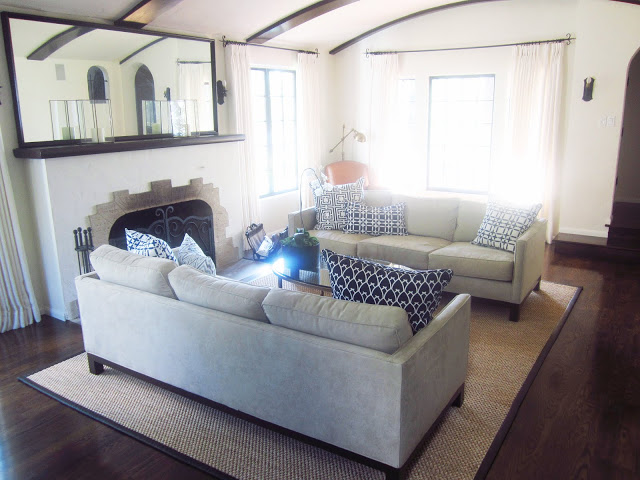 living room with dueling sofas with navy COCOCOZY linen pillows mixed and matched, an oval coffee table, floor length curtains and fireplace with a large mirror on it's mantel