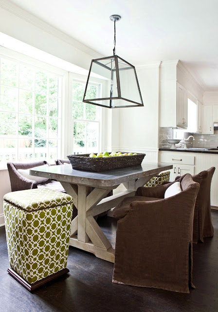 Breakfast nook with a trestle table, metal top, low back upholstered chairs, green graphic patterned stools, and a large brass and glass pendant light