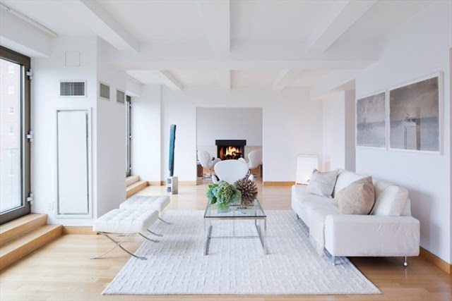 living room in a New York City penthouse apartment designed by John Pawson with light wood floors, a white rug, glass coffee table,white walls and white sofa