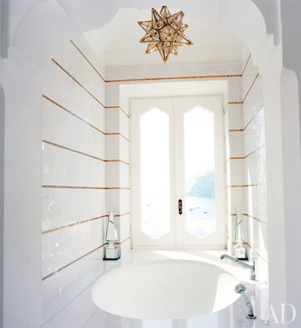 Glamorous gold and white striped bathroom with a step in tub with and a star pendant lamp