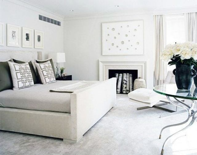 gray bedroom with upholstered bed, a glass table with a large jug of white roses, and molded white fireplace