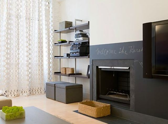 Den with white walls, floating shelves and a fireplace with the fireplace surround painted with chalkboard paint