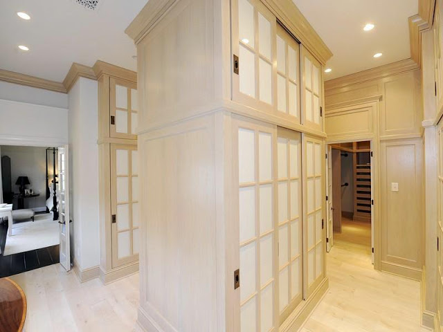 Enormous walk in closet in the master bedroom with light wood storage cabinets and wardrobes