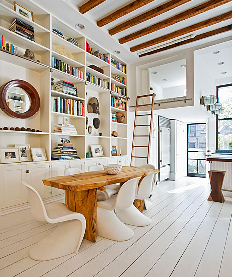 Living room in a home in NYC with wide plank white wood floors, built in bookshelves, a reclaimed wood table surrounded by white S Chairs and exposed beams