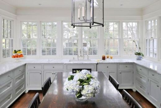 Kitchen with grey cabinets, marble counter tops, casement windows, stained oak table dining room table surrounded by matching chairs and a chandelier