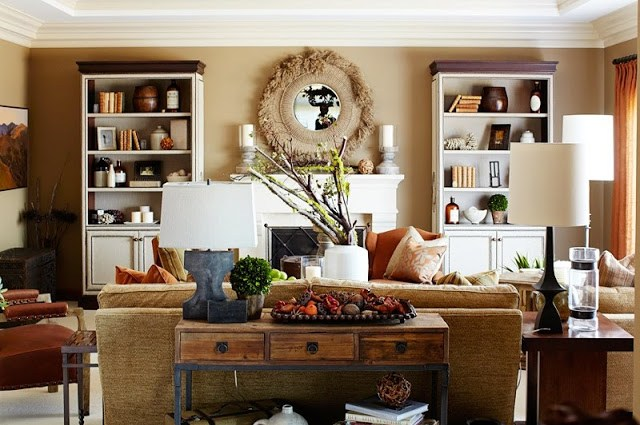polished rustic  decor in a living room with a white modeled fireplace, white bookcase with white cabinets holding books and small keepsakes, a brown sofa with matching armchair and decorative wood table