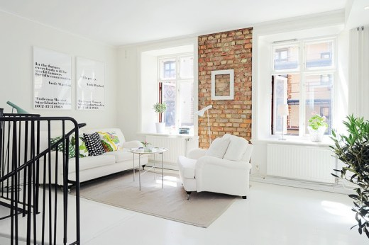 Living room with painted white wood floor, round cofee table, exposed brick wall with an empty white picture frame, a white sofa with bright patterned accent pillows, a white armchair and a taupe rug