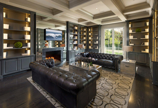 library built in bookshelves coffered ceiling brown leather tufted sofa fireplace dark wood floor