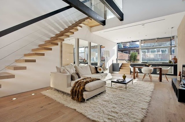 living room with staircase, white sectional sofa and shag rug