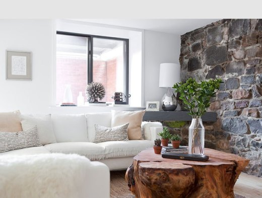 Den with a rock wall, white sofa, silver lamp, and a tree trunk coffee table