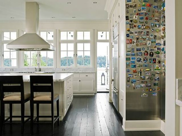 white kitchen with dark wood floor and a stainless steel wall covered in magnets